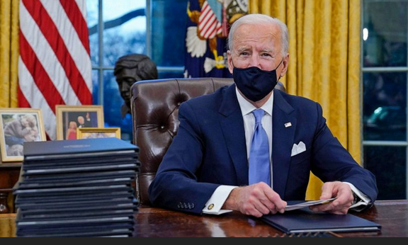 President Biden with a stack of executive orders.
